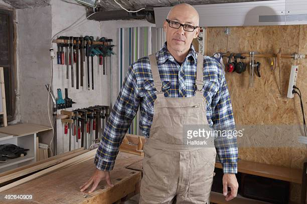 Mature man standing in carpenter shop, portrait