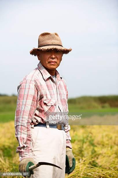 Mature man standing in field, portrait