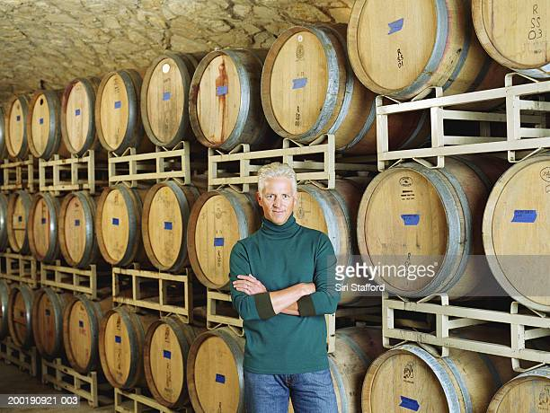 Mature man standing in front of barrels in winery