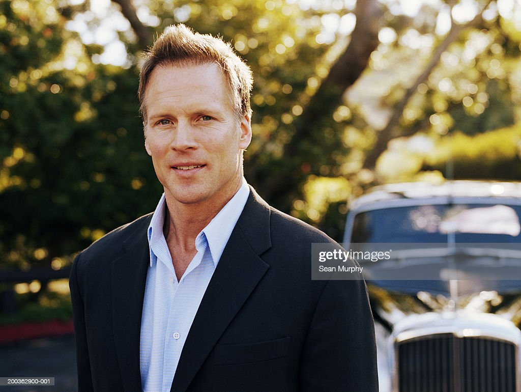 Mature man standing in front of car, portrait : Stock Photo