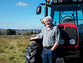 Mature man standing in front of tractor, portrait