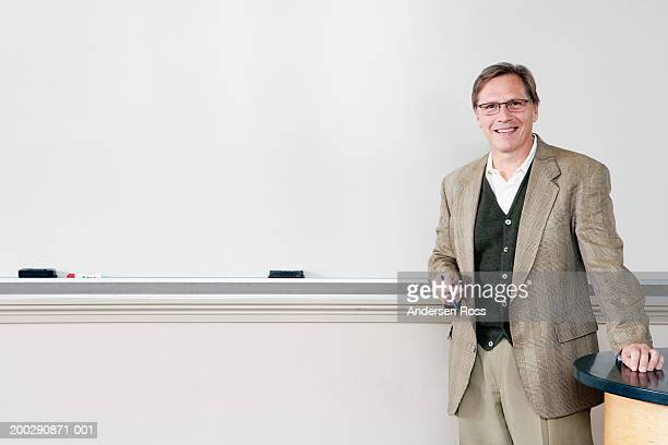 Mature man standing in front of whiteboard, smiling, portrait