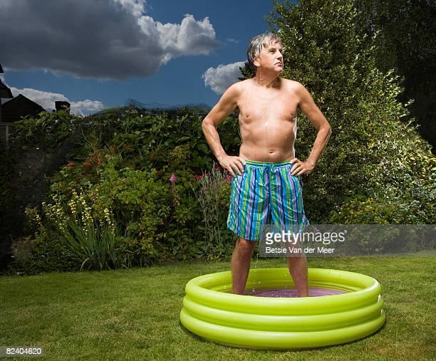 Mature man standing in paddlingpool.