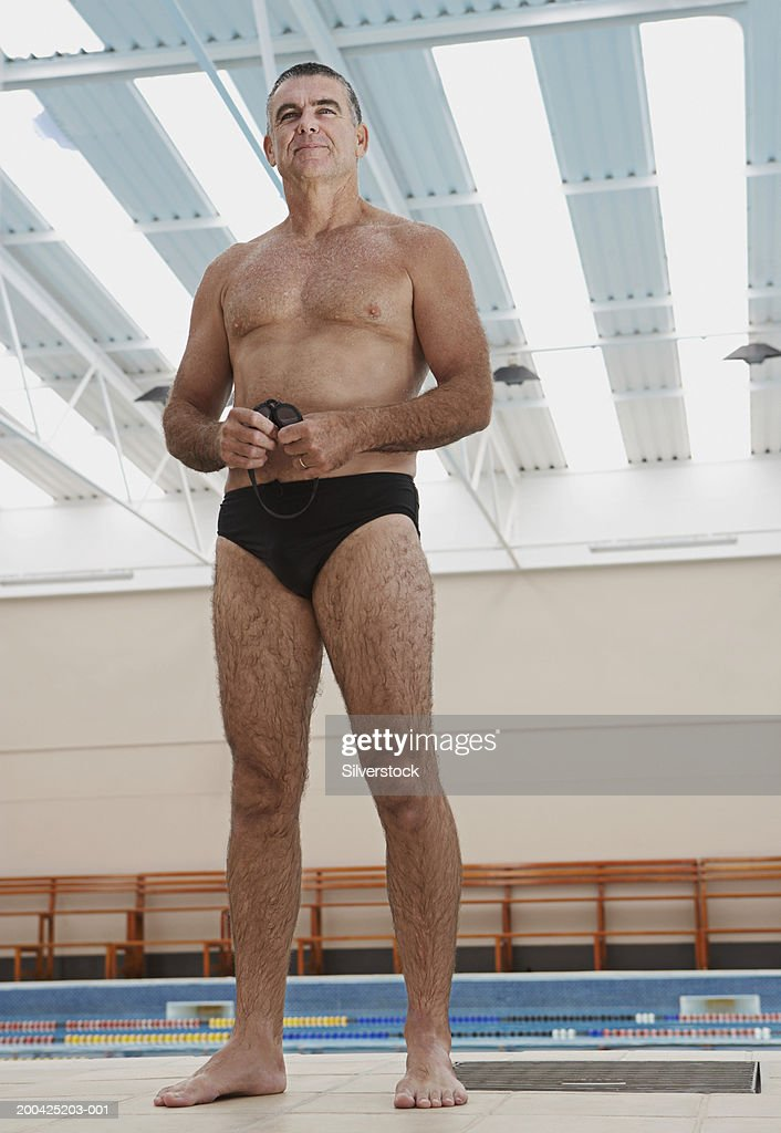 Mature man standing in public swimming baths, low angle view