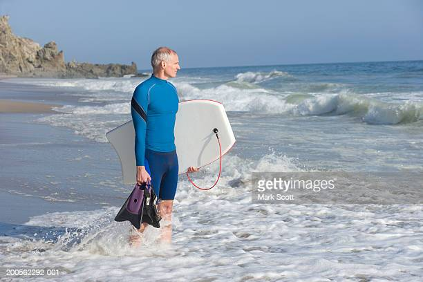 Mature man standing in sea holding surfboard