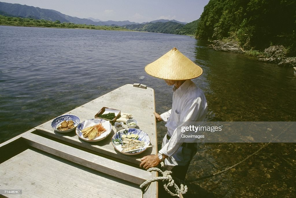 Mature man standing near a boat, Shimanto River, Kochi, Shikoku, Japan
