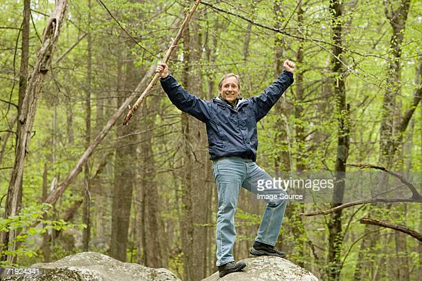 Mature man standing on a rock in forest