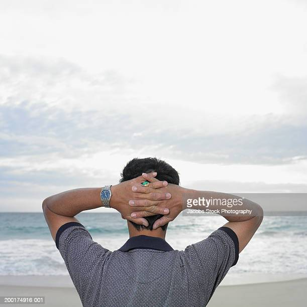 Mature man standing on beach, hands clasped behind head, rear view