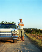 Mature man standing on track leaning against convertible car, portrait