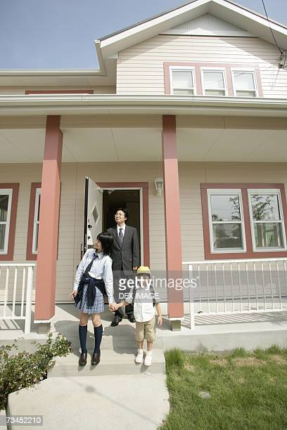 Mature man stepping out of the house with his son and daughter