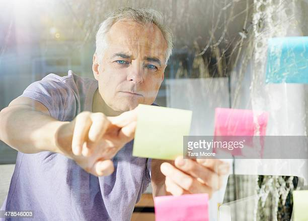 mature man sticking down lost it note