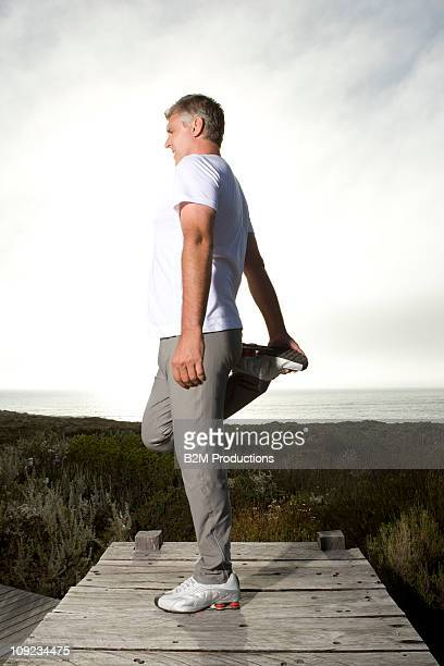 Mature man stretching on jetty