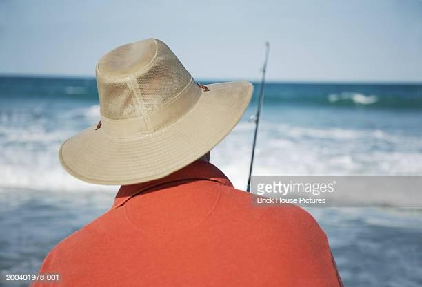 Mature man surf fishing, rear view