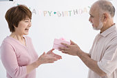 Mature man surprising wife with birthday gift, smiling, side view