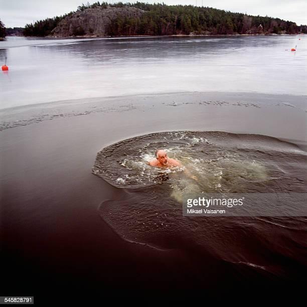 Mature Man Swimming in Frozen Lake