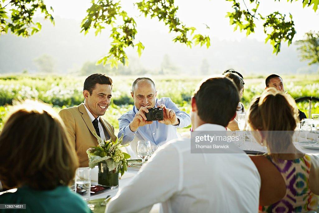 Mature man taking digital photo of friends : Stock Photo