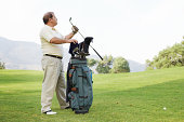 Mature man taking golf club from bag