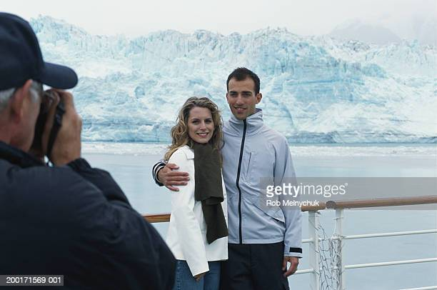Mature man taking photograph of couple embracing on balcony of ship