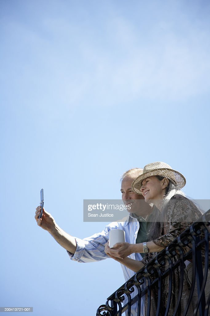 Mature man taking picture on balcony with camera phone, low angle view