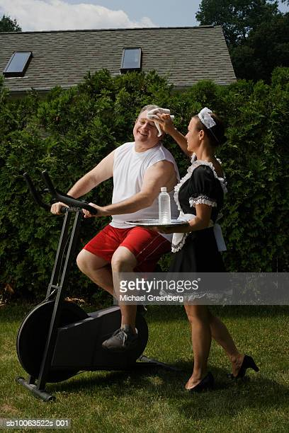 Mature man training on exercise bike in garden, maid wiping his forehead, holding tray with water bottle
