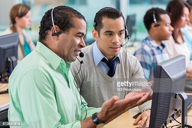 Mature man trains new employee in call center
