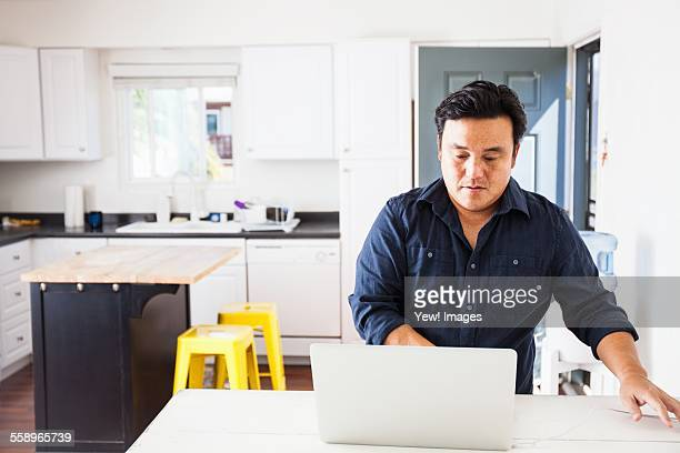 Mature man typing on laptop at kitchen table