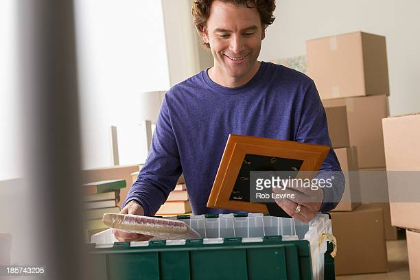 Mature man unpacking picture frame from crate