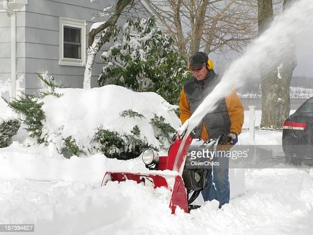 Uomo maturo utilizzando un soffiatore di neve.