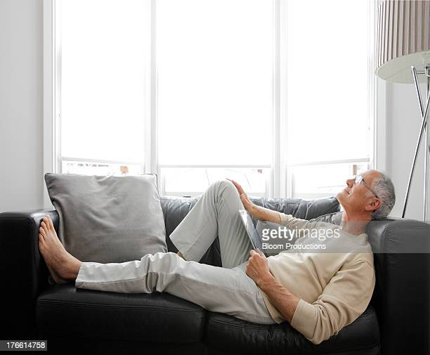 Mature man using a tablet relaxed on the sofa
