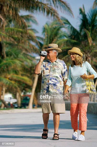 Mature man using a video camera walking with a mature woman