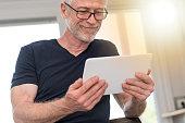 Mature man using digital tablet at home, light effect
