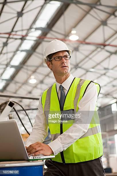 Mature man using laptop in factory