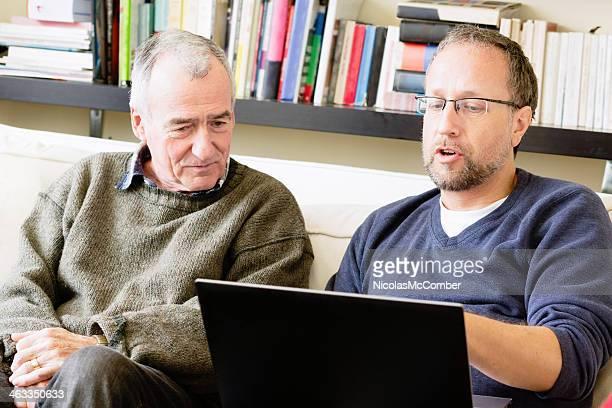 Mature man using laptop in social conversation