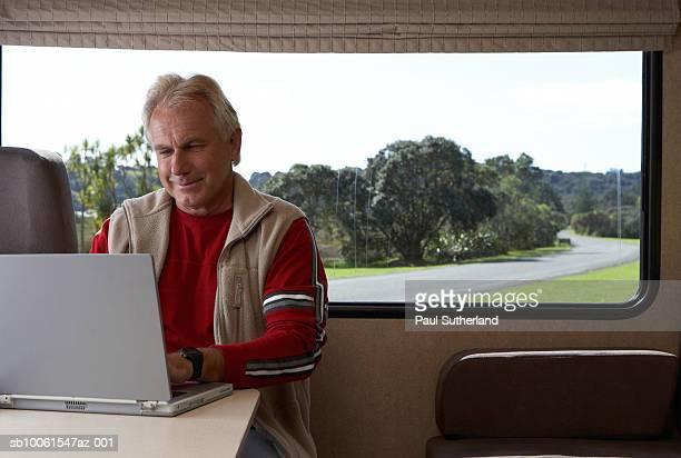 Mature man using laptop inside motor home