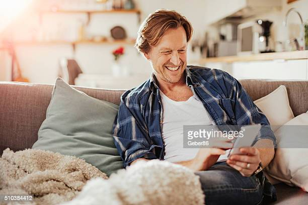 Mature man using mobile phone at home
