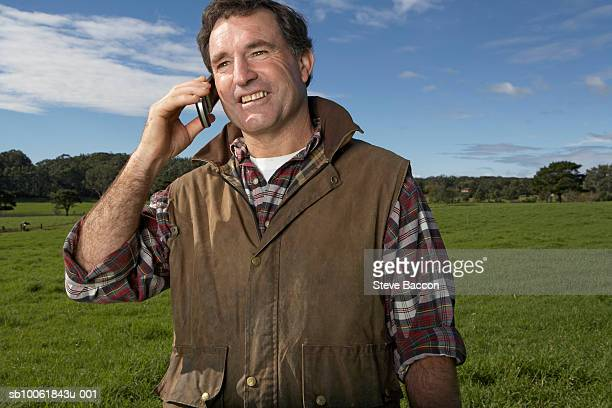 Mature man using mobile phone on meadow, smiling