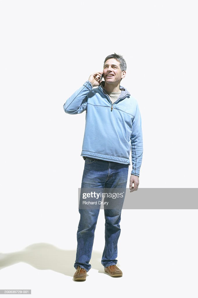 Mature man using mobile phone, smiling : Stock Photo
