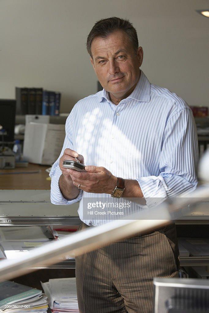 Mature man using palmtop in office, raising eyebrow, portrait : Stock Photo