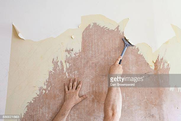 Mature man using scraper to scrape off old wallpaper