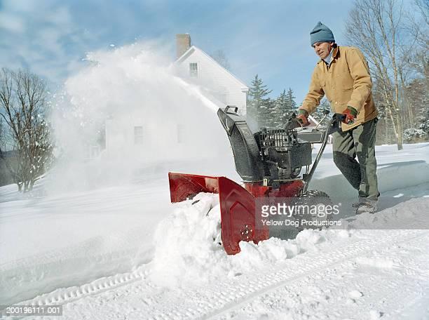 Mature man using snowblower outside home, winter