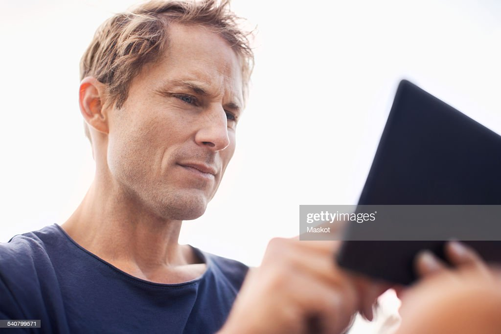 Mature man using tablet computer against clear sky