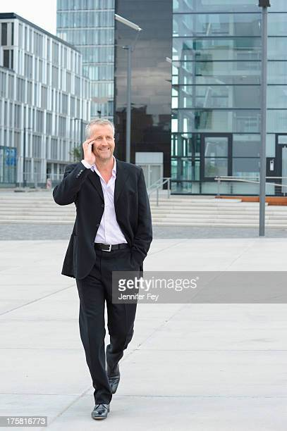 Mature man walking in financial district and using cellphone
