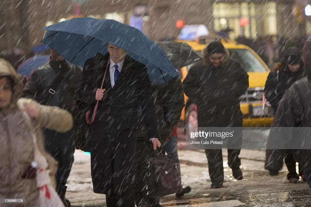 Mature man walking in the street during snow : Stock Photo
