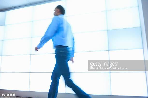 Mature man walking past backlit wall panels