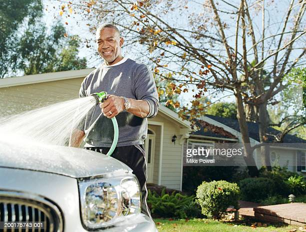 Mature man washing car in driveway, portrait