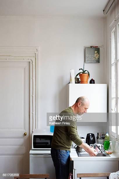 Mature man washing up in kitchen