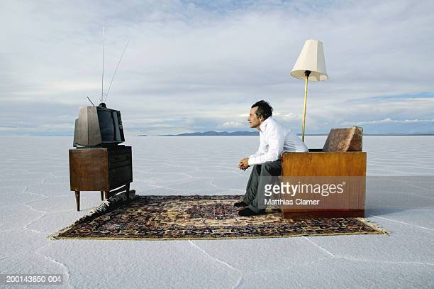 Mature man watching television on salt flat, side view