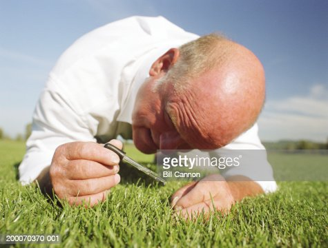 Mature man watering lawn with eye dropper, ground view : Stock Photo