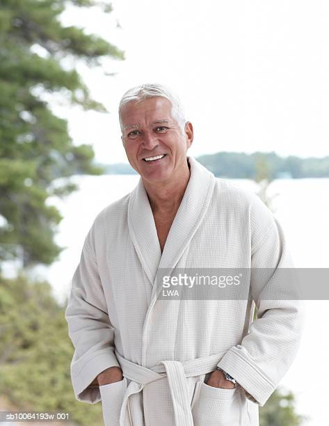 Mature man wearing bathrobe standing by lake, smiling, portrait
