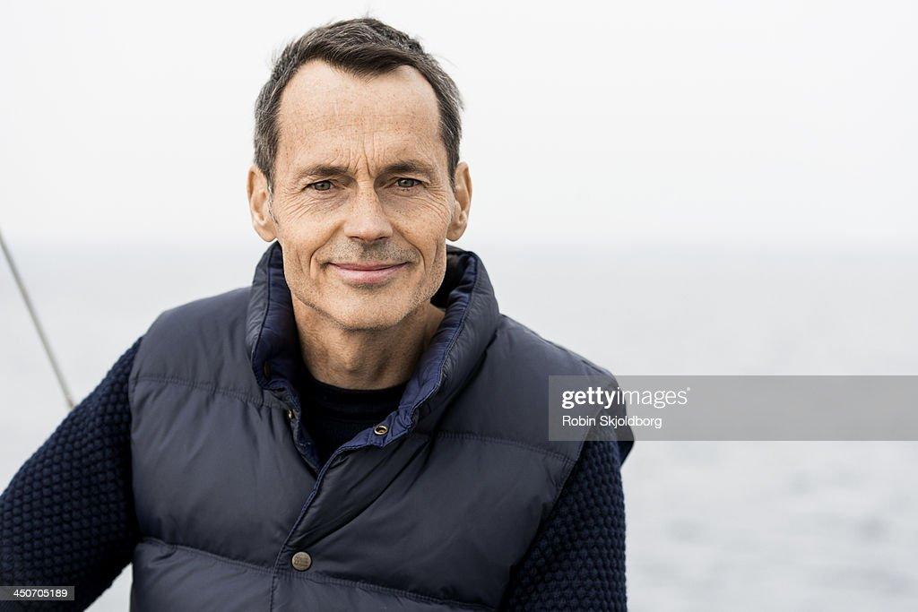 Mature man wearing blue vest smiling